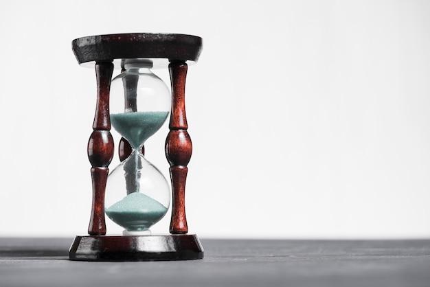 Zandloper op grijs bureau dat de laatste seconde of de laatste minuut of de time-out toont Gratis Foto