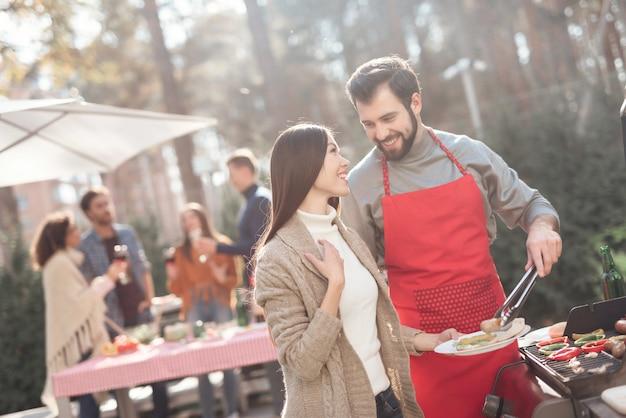 Ze hebben plezier, koken voedsel, drinken alcohol. Premium Foto
