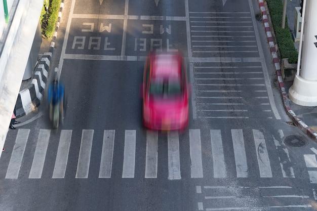 Zebrapad en auto, bezige stadsstraat en auto in motieonduidelijk beeld op zebrapad Premium Foto