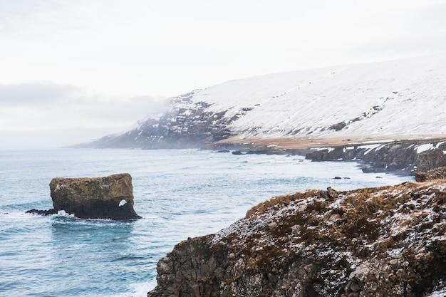 Zee omgeven door heuvels bedekt met sneeuw en mist onder een bewolkte hemel in ijsland Gratis Foto