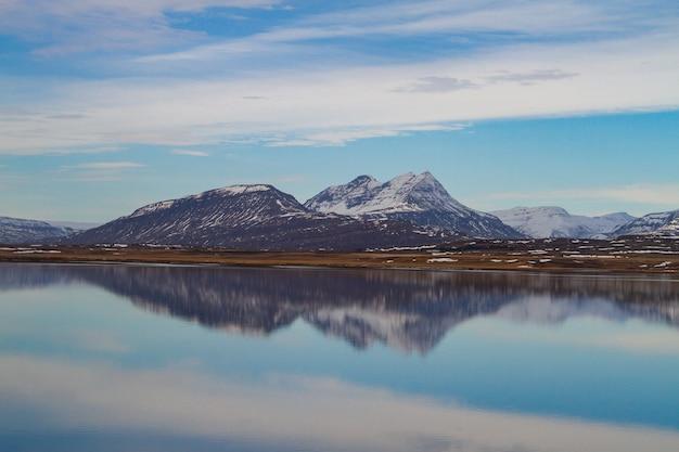 Zee omgeven door rotsachtige bergen bedekt met de sneeuw en nadenken over het water in ijsland Gratis Foto