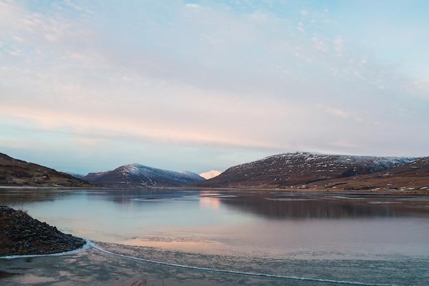 Zee omgeven door rotsen bedekt met de sneeuw en nadenken over het water in ijsland Gratis Foto