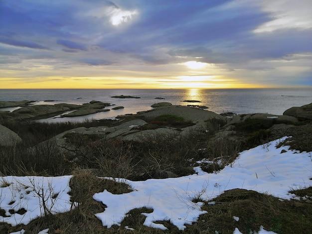 Zee omgeven door rotsen onder een bewolkte hemel tijdens de zonsondergang in rakke in noorwegen Gratis Foto