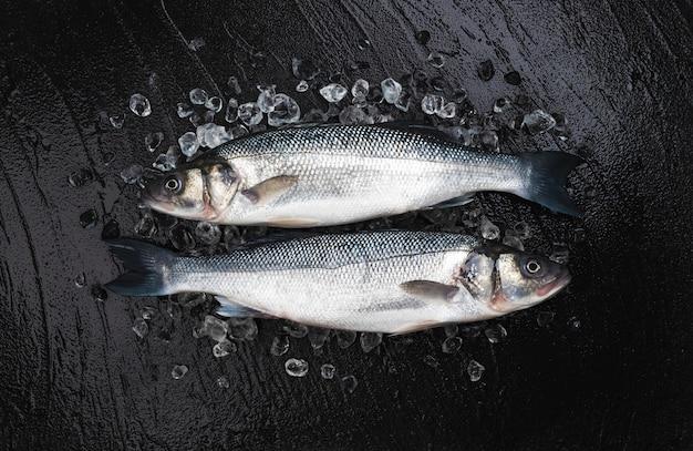Zeebaars op ijs op zwarte stenen achtergrond, bovenaanzicht Premium Foto