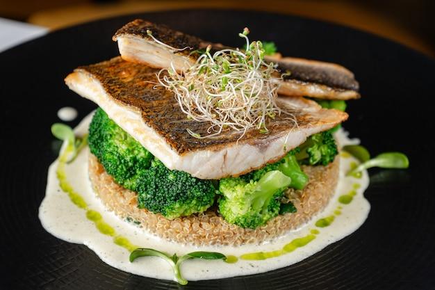 Zeebaarsfilet met broccoli en quinoa op zwarte plaat Premium Foto