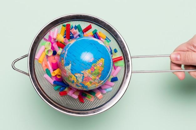 Zeef met plastic en wereldbol Gratis Foto