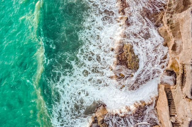 Zeegezicht met golven die tegen de rotsen breken Gratis Foto