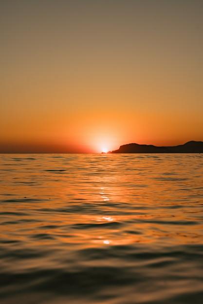Zeegezicht met heldere hemel en golven op zonsondergang Gratis Foto