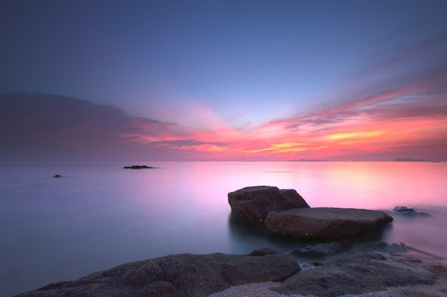 Zeegezichtzonsondergang met fantastisch rotsoppervlak en rode hemel, lange blootstellingstechniek Premium Foto