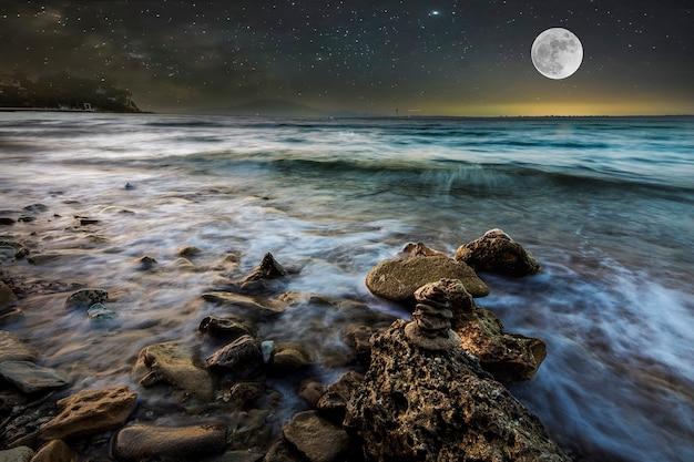 Zeegolven op het steenachtige strand 's nachts met een sterrenhemel en een volle maan Premium Foto