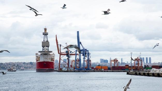 Zeehaven met afgemeerd vrachtschip bij bewolkt weer met vliegende zeemeeuwen, turkije Premium Foto