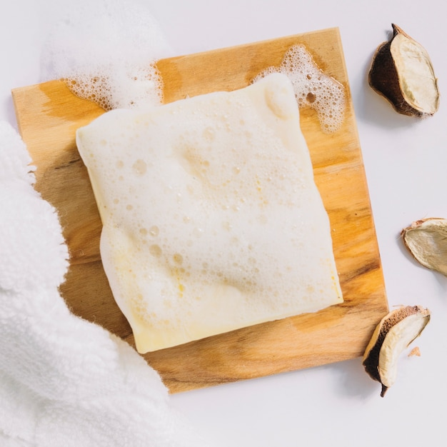 Zeepstaaf met schuim op houten raad dichtbij handdoek en katoenpeulen Gratis Foto