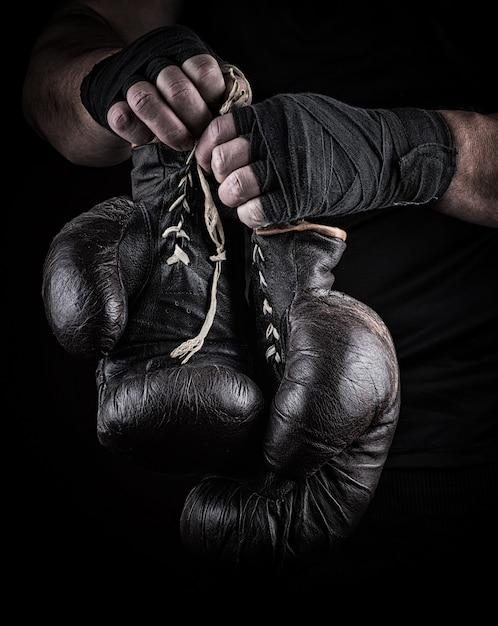 Zeer oude boks sport handschoenen in handen van mannen Premium Foto