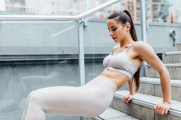 Zeer sexy, fit atletische vrouw oefent haar bovenlichaam tijdens een bootcamp-training. Premium Foto