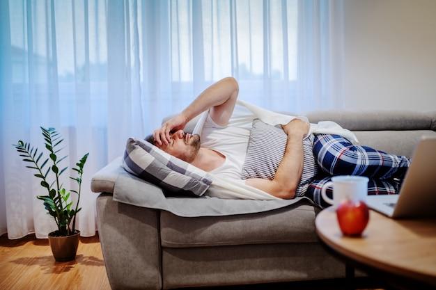 Zeer zieke blanke man in pyjama en bedekt met deken liggend op de bank in de woonkamer, kussen te houden en buikpijn te hebben. Premium Foto