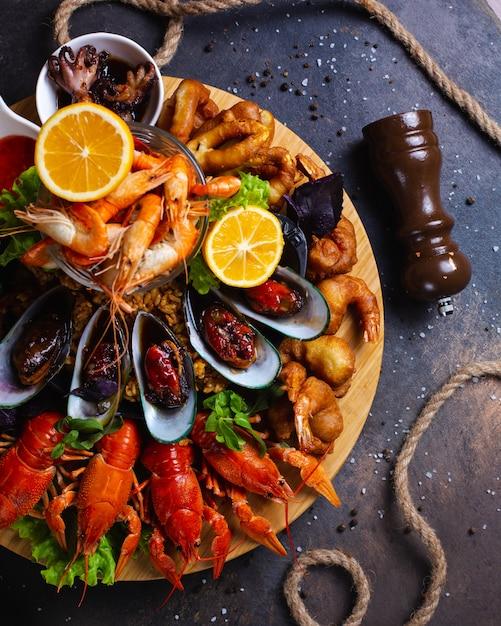 Zeevruchten bord met garnalen, mosselen, kreeft geserveerd met citroen Gratis Foto