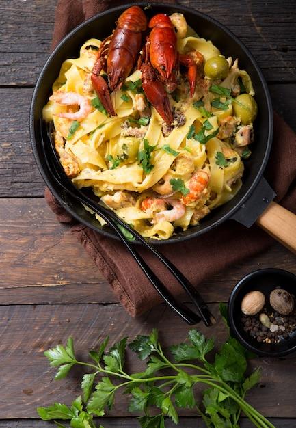 Zeevruchten fettuccine pasta met rivierkreeftjes, octopus garnalen, op stenen pan. gastronomisch gerecht Premium Foto