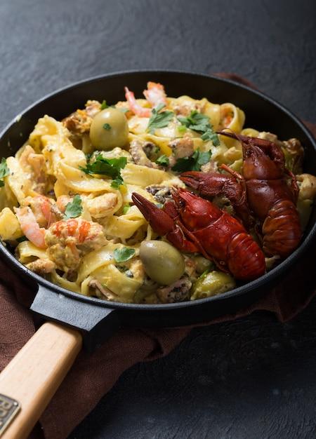 Zeevruchten fettuccine pasta met rivierkreeftjes, octopus shrims, op stenen pan. gastronomisch gerecht Premium Foto