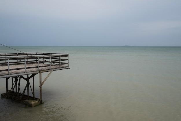 Zeewater en blauwe hemel samen met houten pier Gratis Foto