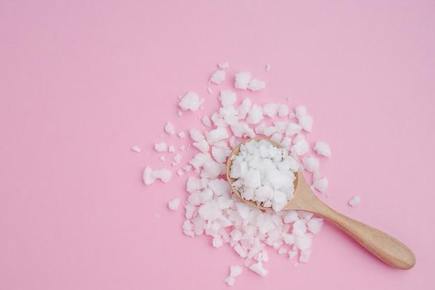 Zeezout in een houten lepel op roze achtergrond Premium Foto