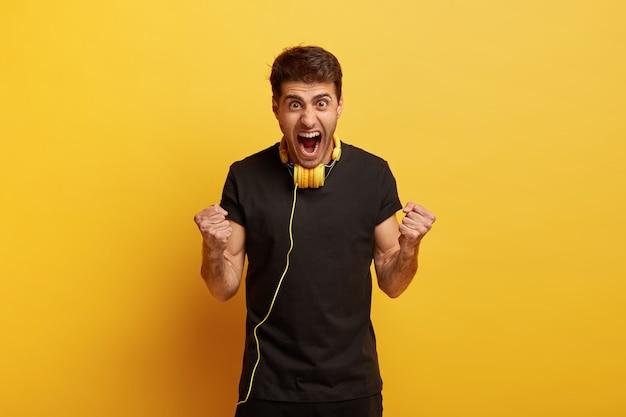 Zeg ja tegen geweldig geluid. dolblij emotionele jonge blanke man balde vuisten, schreeuwt luid, draagt een zwart t-shirt Gratis Foto