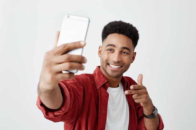Zeg kaas. sluit omhoog van de jonge mooie donkerhuidige mens met afrokapsel in toevallig wit t-shirt en rood overhemd glimlachend met tanden, houdend smartphone, makend selfie foto. Gratis Foto