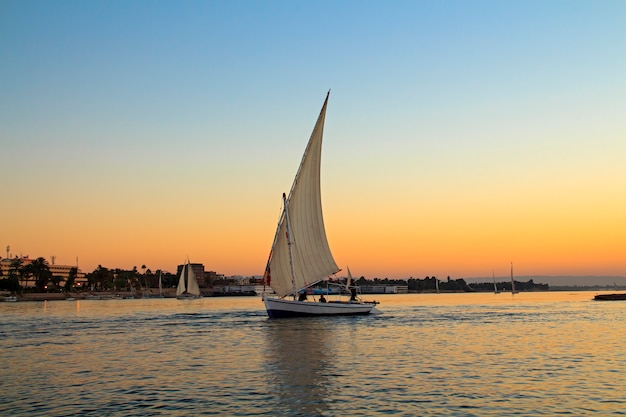 Zeilboot bij zonsondergang in de nijl, egypte Premium Foto