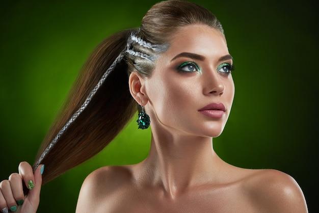 Zeker mooi donkerbruin meisje met modieus kapsel met elementen van zilveren kleuren en het groene glanzende make-up stellen. vrouw met grote ronde oorbel wegkijken, haar in de hand houden. schoonheid. Premium Foto