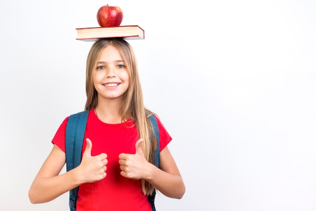 Zeker schoolmeisje in evenwicht brengend boek op hoofd Gratis Foto