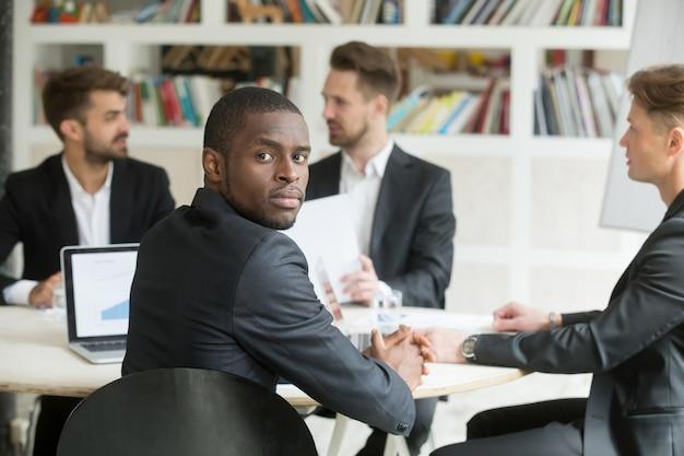 Zekere afrikaanse amerikaanse zakenman die camerazitting op vergadering bekijkt Gratis Foto