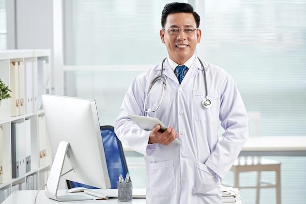 Zekere arts die camera bekijkt die tabletpc houdt Gratis Foto