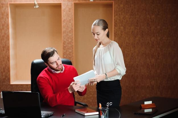 Zekere baas met papier iets uit te leggen aan secretaresse Premium Foto