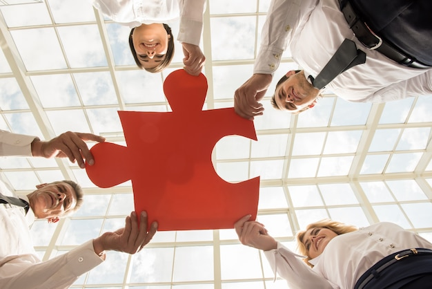 Zekere bedrijfsmensen die puzzel samen houden. Premium Foto