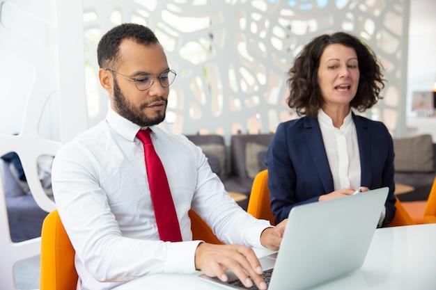 Zekere bedrijfsmensen die tijdens vergadering spreken Gratis Foto
