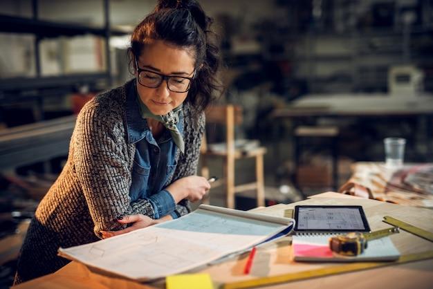 Zekere ernstige aantrekkelijke professionele architectenvrouw die tegen het bureau leunen en in het nieuwe project met nota's, tablet en heersers op de lijst in de stoffenplaats kijken. Premium Foto