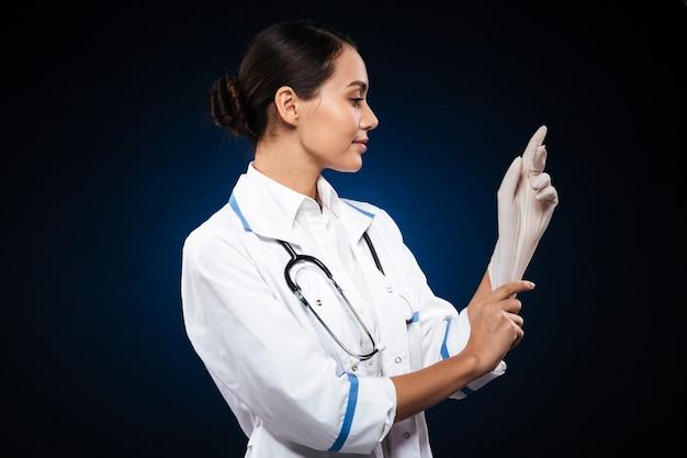 Zekere glimlachende arts die medische geïsoleerde handschoenen draagt Gratis Foto