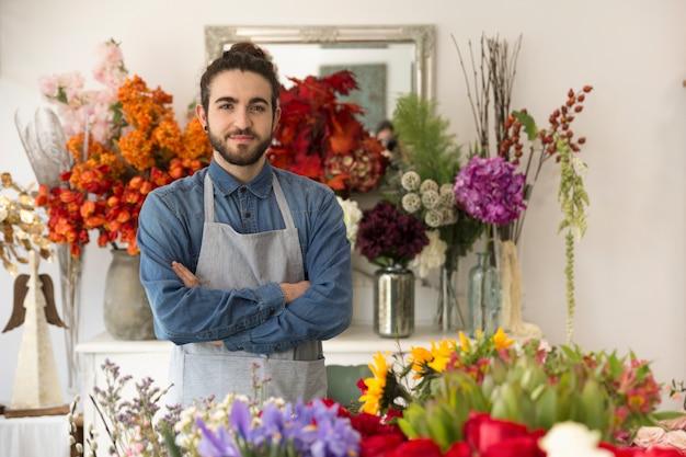 Zekere glimlachende jonge mannelijke bloemist met kleurrijke bloemen in zijn winkel Gratis Foto