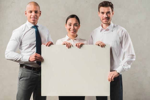 Zekere glimlachende jonge onderneemster met zijn twee collega's die leeg aanplakbiljet houden Gratis Foto