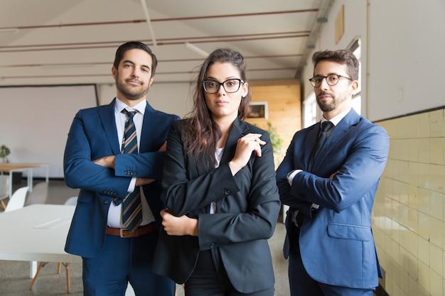 Zekere jonge bedrijfsmensen die met gekruiste wapens stellen Gratis Foto