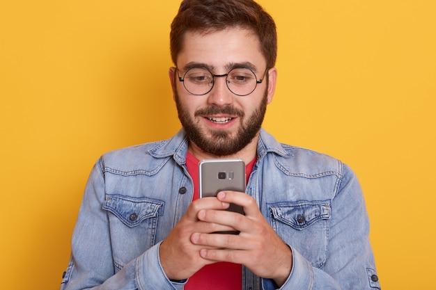 Zekere jonge gebaarde opgewekt status tegen gele muur, houdend slimme telefoon in handen, lezend bericht van zijn vriendin Gratis Foto