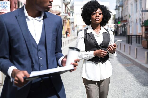 Zekere jonge onderneemster die digitale tablet houdt lopend met zijn collega in de stad Gratis Foto