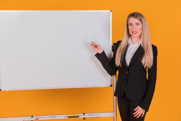 Zekere jonge onderneemster die presentatie geeft tegen een oranje achtergrond Gratis Foto