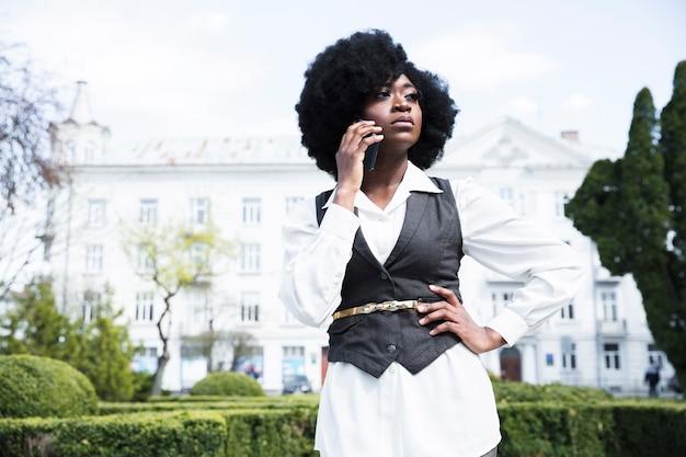 Zekere jonge onderneemster met haar handen op heup die op mobiele telefoon spreken Gratis Foto
