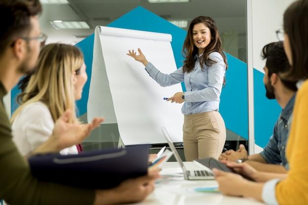 Zekere jonge teamleider die een presentatie geeft aan een groep jonge collega's terwijl ze zitten gegroepeerd op de flip-over in het kantoor Premium Foto