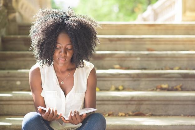 Zekere jonge vrouw lezen tijdschrift op trappen Gratis Foto