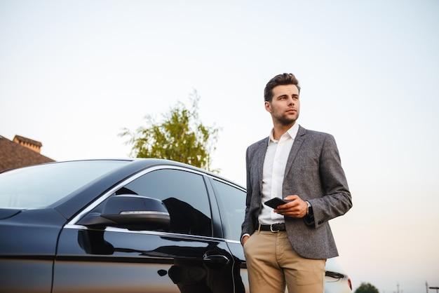 Zekere jonge zakenman in kostuum dat zich bij zijn auto bevindt Premium Foto