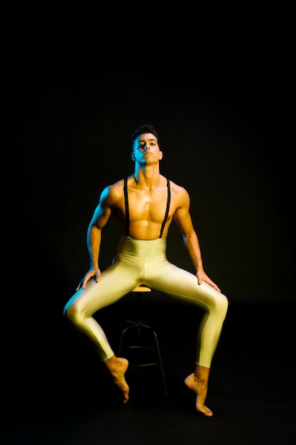 Zekere mannelijke balletdanserzitting in schijnwerper Gratis Foto