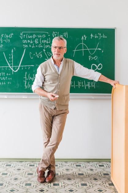 Zekere oude wiskundeleraar die klasse bekijkt Gratis Foto