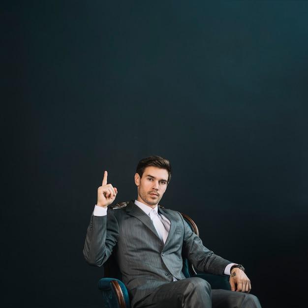 Zekere slimme jonge zakenmanzitting op leunstoel die vinger benadrukken tegen zwarte achtergrond Gratis Foto