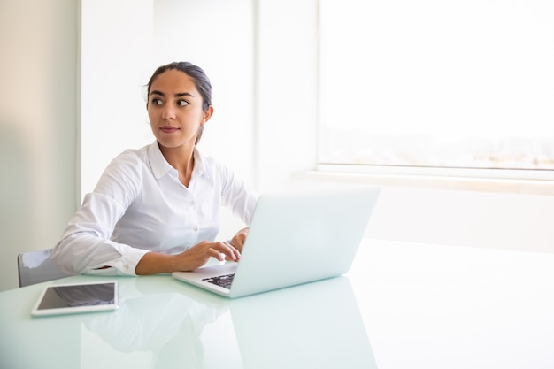 Zekere vrouwelijke adviseur die aan computer werkt Gratis Foto